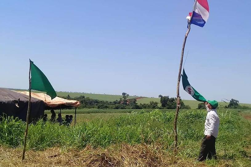 Un campesino levanta la bandera paraguaya con orgullo.